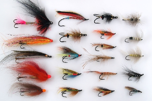 Salmon flies. Left vertical row: tube flies are especially popular for fly-fishing on the salmon rivers in the areas of Gulf of Finland and Gulf on Bothnia. Second and third row: different kind of salmon flies, that are used e.g. on River Teno for casting and trolling. Right row up: three dry flies for salmon.